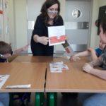 Wychowawczyni prezentująca flagę polski grupie przedszkolaków.