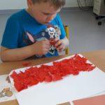 Uczeń wyklejający flagę polski za pomoca bibuły.