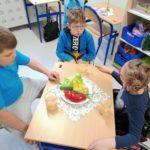 Uczniowei siedżacy przy stoliku zastawionym zdrowymi składnikami na II śniadanie.