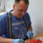 Podopieczny podczas czynności krojenia pomidorów.