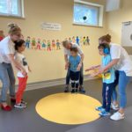 Grupa przedszkolaków wraz z nauczycielami podczas zabawy muzyczno - ruchowej.