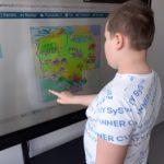 Uczeń układający puzzle mapy polski na tablicy interaktywnej.