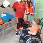 Ratownik medyczny oraz uczeń poruszający się na wózku inwalidzkim podczas prezentacji strojów służb mundurowych.