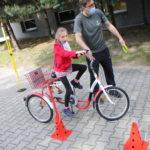 Przedszkolak pokonujący tor przeszkód na trójkowłowym rowerze z asekuracją nauczyciela.