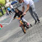 Przedszkolak na rowerze czterokołowym w asyście nauczyciela.