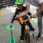 Uczennica wukonująca z pomoca zadanie koordynacyjne na czterokołowym rowerze.