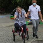 Uczennica jadąca na trójkołowym rowerze z asystą nauczyciela.