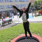 Uczeń skaczący na trampolinie naziemnej.