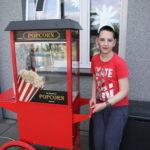Uczeń pozujący z maszyną do popcornu.