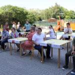 """Absolwenci siędzący przy """"egzaminacyjnych"""" stołach na szkonym podwórku."""
