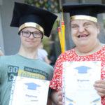 Uczniowei pozujący w biretach absolwenta z dyplomami.