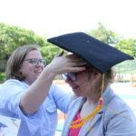 Wychowawca nakładający uczennicy biret absolwent.