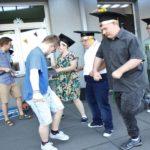 Absolwenci tańczący na szkolnym tarasie.