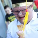Uczeń w birecie absolwenta pozujący z porcją lodów.