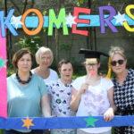 Uczniowie wraz z nauczycielami pozujący w kolorowej ramce z napisem Komers