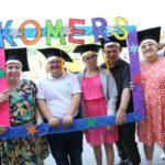 Uczniowie wraz z nauczycielem pozujący w kolorowej ramce z napisem Komers.