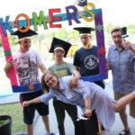 Uczniowie wraz z nauczycielami pozujący w kolorowej ramce z napisem Komers.