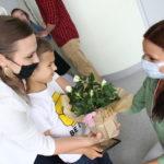 Przedszkolak wraz z rodzicem podczas wręczania kwiatów wychowawcy.