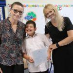 Uczeń preznetujący świadectwo wraz z wychowawcą i pomocą nauczyciela.