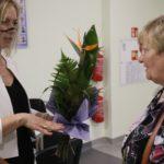 Przedstawicielka Rady Rodziców wręczająca kwiaty dyrekcji placówki.