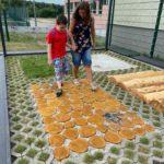 Przedszkolak pokonujący ścieżkę sensoryczną z asekuracją wychowawcy.