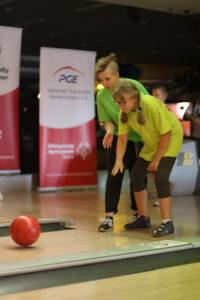 Uczestnicy turnieju w trakcie rzutu kulą bowlingową.