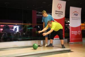 Uczestnik turnieju wraz z asystą w trakcie rzutu kulą bowlingową.