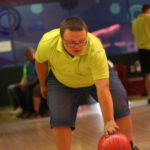Uczestnik turnieju w trakcie rzutu kulą bowlingową.