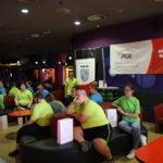Uczestnicy turnieju bowlingowego siedzący przy stolikach na poszczególnych torach bowlingowych. W tle Banery z logortypami Olimpiad Specjalnych Miasta Rybika oraz PGE.