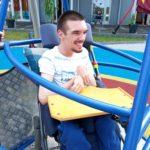 Podopieczny huśtający się na huśtawce dla osób poruszających się na wózkach inwalidzkich.