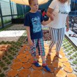 Uczeń pokonujący ścieżkę sensoryczna z asekuracją wychowawcy.