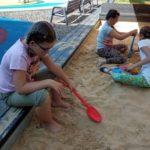 Uczennice bawiące się w piaskownicy.
