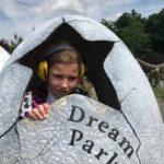 Uczennica pozująca w mega jaju dinozaura z napisem Dream Park.