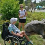 Uczeń wwraz z nauczycielem pozyjący z figurą dinozaura.