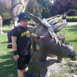 uczeń pozujący z figurą dinozaura.