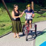 Uczeń na rowerze tr ojkołowym z asekuracją nauczycielki.