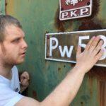 Uczeń obserwujący oznaczenie numeryczne zabytkowej lokomotywy.