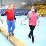 Młody sportowiec podczas aktywności pokonania ławeczki równoważnej.