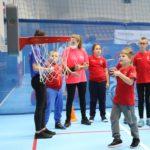 Młody sportowiec podczas aktywności rzutu piłką do kosza.
