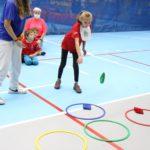 Młody sportowiec podczas aktywności rzutu do celu woreczkiem gimnastycznym.