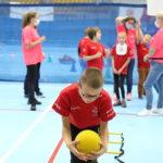 Młody sportowiec podczas aktywności nakładania skoku w przód z piłką.