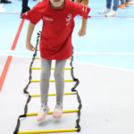 Młody sportowiec podczas aktywności skoku przód ponad płaskimi poprzeczkami.