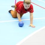 Młody sportowiec podczas aktywności toczenia piłki w pozycji czworaczej.