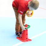 Młody sportowiec podczas aktywności nakładania kółka na pachołek.