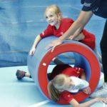"""Młodzi sportowcy podczas aktywności toczenia w """"beczce""""."""