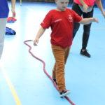 Młody Sportowiec podczas wykonania zadania chód stopa za stopa po linie.