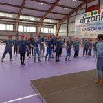 """Ekipa uczestników imprezy """"Bądź fit"""" OS w Dżonkowie podczas zajęć aerobiku."""